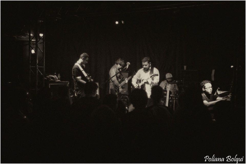 Foco em preto e branco, de um show. Músicos no palco, iluminados, e todo o entorno, incluindo a plateia, escuro.
