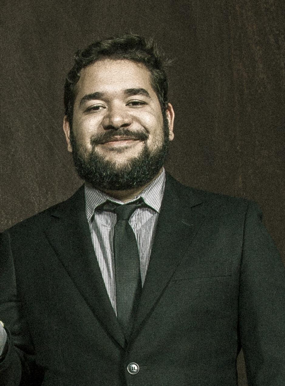 Homem de barba, terno e gravata, olhando para a câmera.