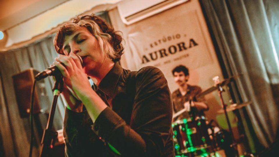 """Cantora Letty em primeiro plano, de olhos fechados e segurando o microfone. Ao fundo, um baterista e sua bateria, e a inscrição """"Estúdio Aurora"""" acima, na parede."""