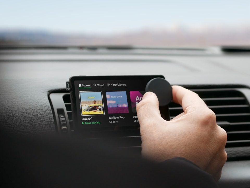 Car Thing acoplado ao painel de um carro, com uma mão mexendo em seu botão giratório.